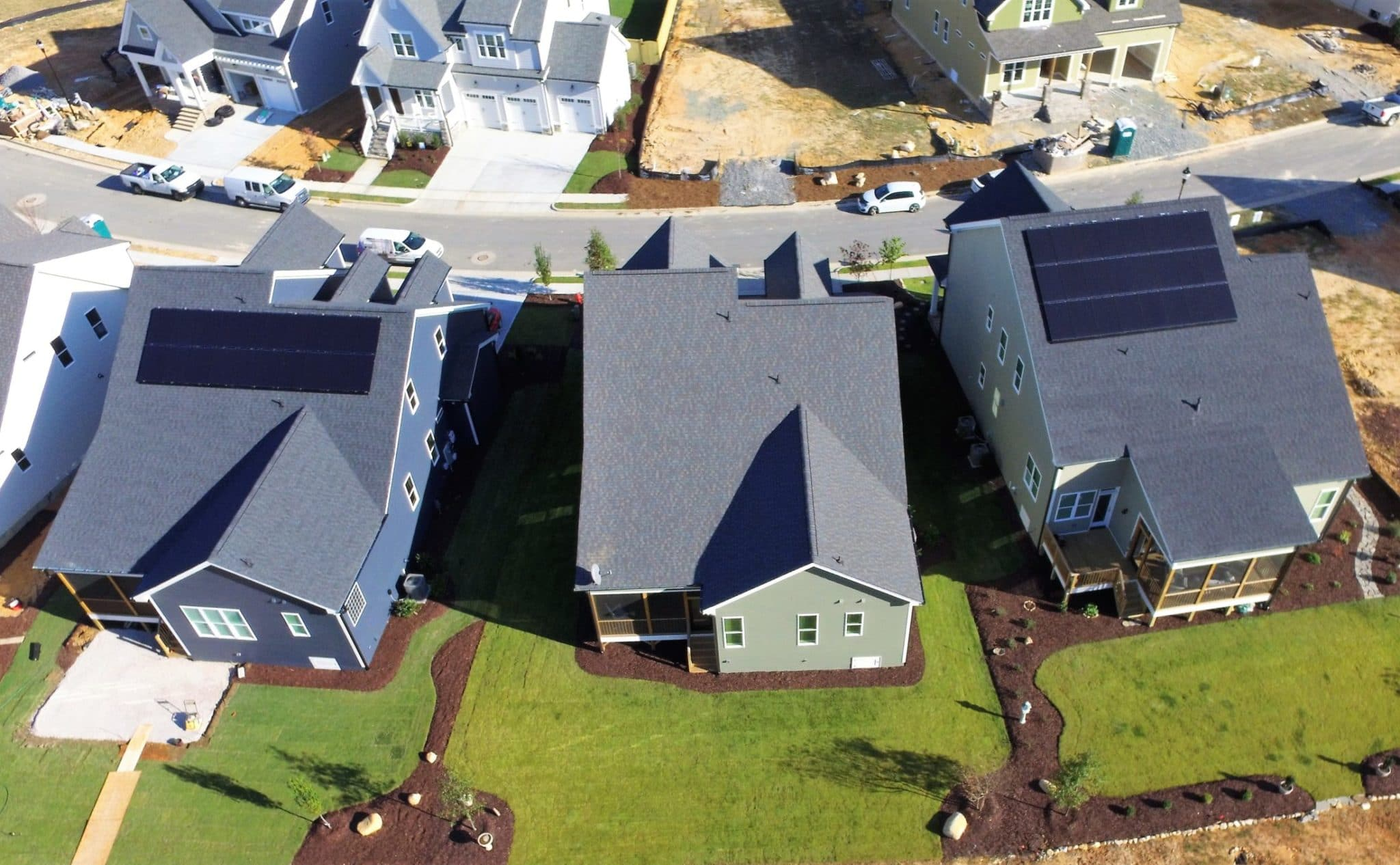 Neighborhood street with two homes with solar
