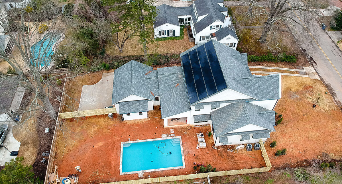 Aerial view of a roof mounted solar system on a new construction home with a pool in north carolina