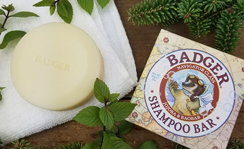 Badger balm shampoo bar on a towel surrounded by natural herbs
