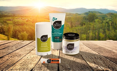 All Good brand deodorant, sunscreen, lip balm, and cream sitting on a wood table overlooking a mountain sunset