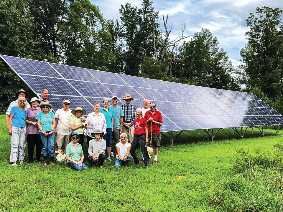 Residents from Elderberry Cohousing standing in front of community ground mount solar system