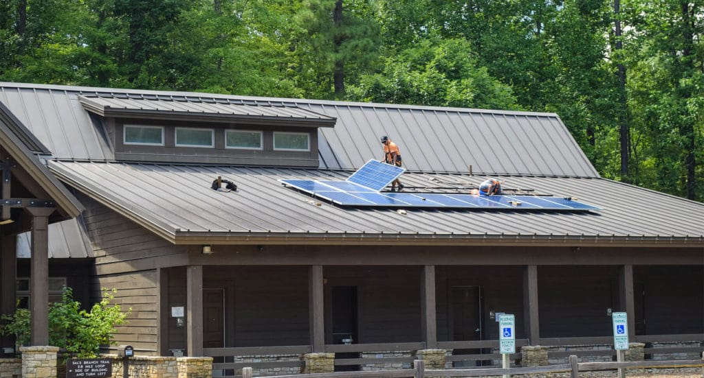 Solar installers from Southern Energy Management on the roof of the visitors center at Umstead State Park laying the solar panels in place