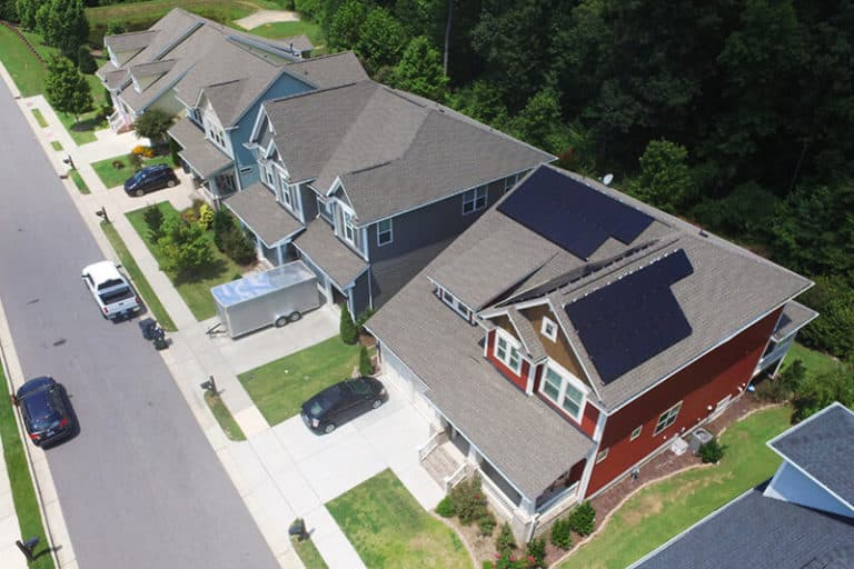 Aerial view of a black roof solar system on a red house