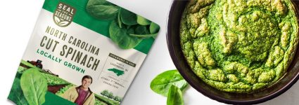 A bowl of spinach souffle next to a bag of Seal the Seasons north carolina grown spinach
