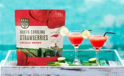 Two glasses of strawberry margaritas next to a bag of Seal the Seasons North Carolina Grown strawberries
