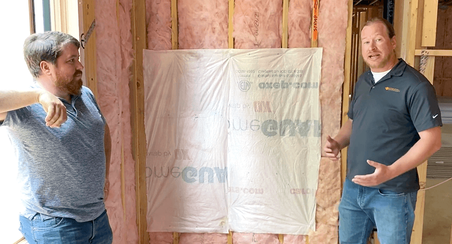 Michael and Matt next to a demo wall showing house wrap used as a flexible air barrier
