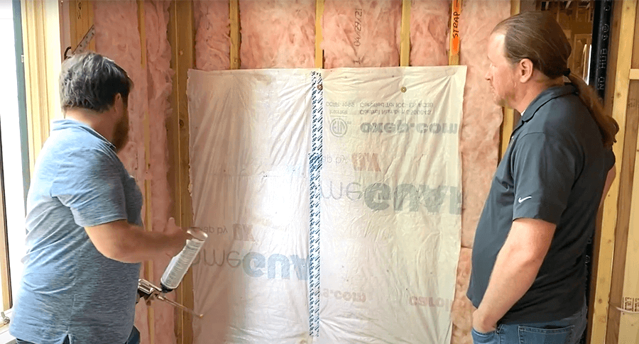 Michael demonstrating how to apply foam to the outer edge of a flexible air barrier