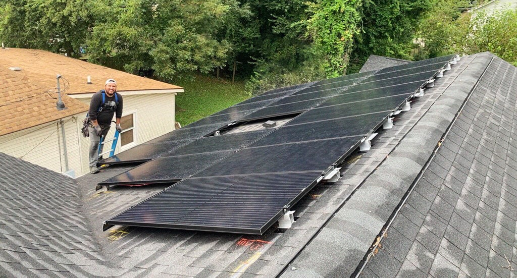 Solar installer on a roof with a home solar system
