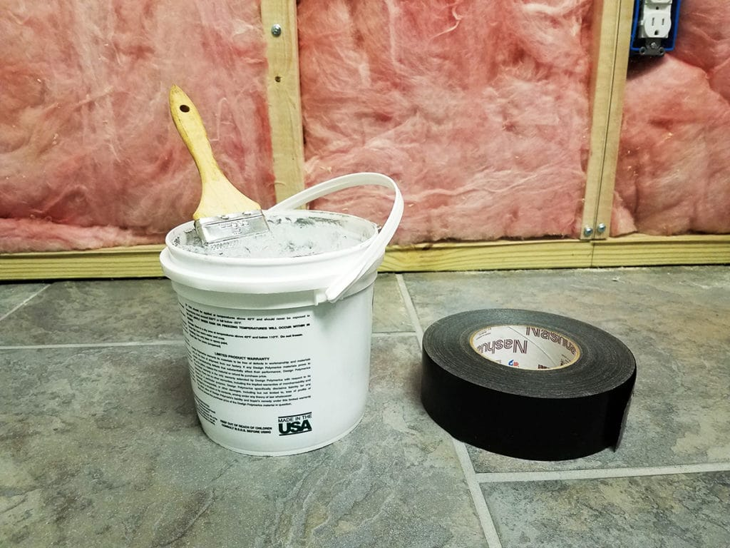 Bucket of mastic next to roll of duct tape