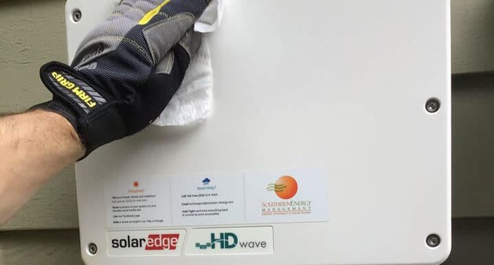 Solar installer wearing gloves and cleaning an inverter for COVID-19 safety