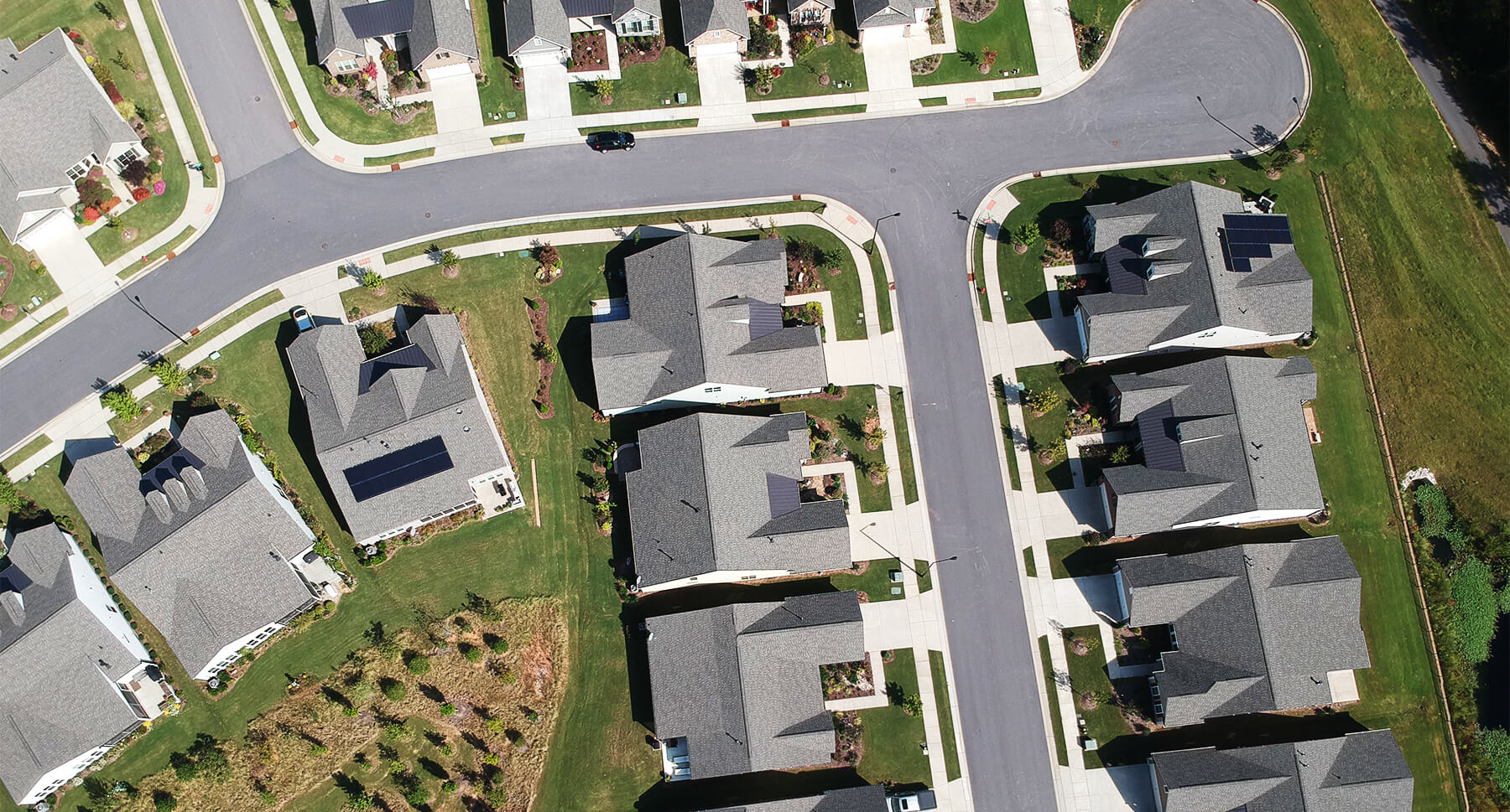 Aerial view of a neighborhood street with two homes that have solar systems