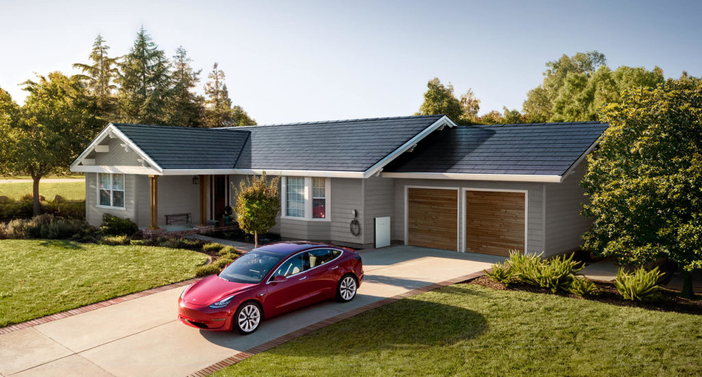 Tesla solar shingle roof with a powerwall system on a one story home with a Tesla electric vehicle in the driveway