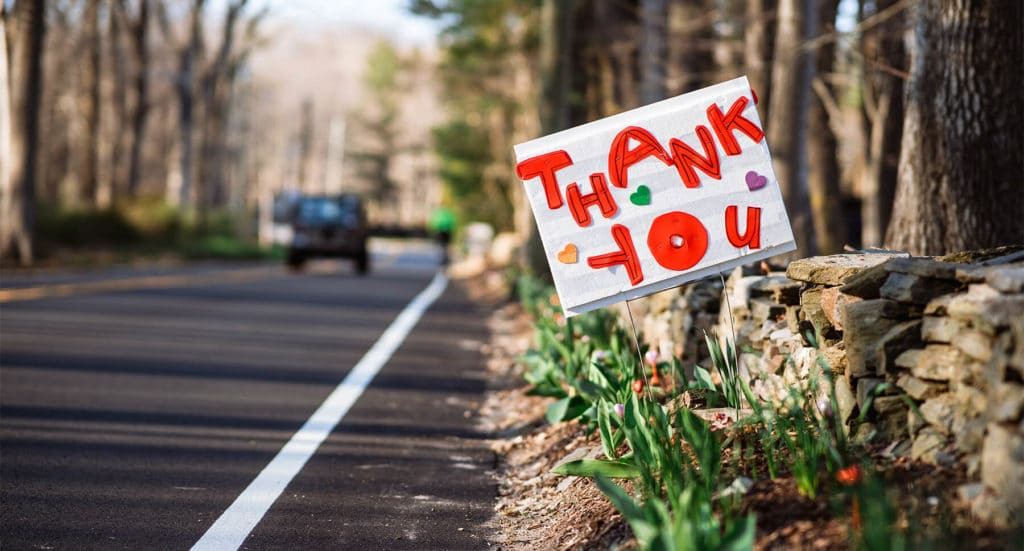 Thank you sign on the side of the road with blooming flowers